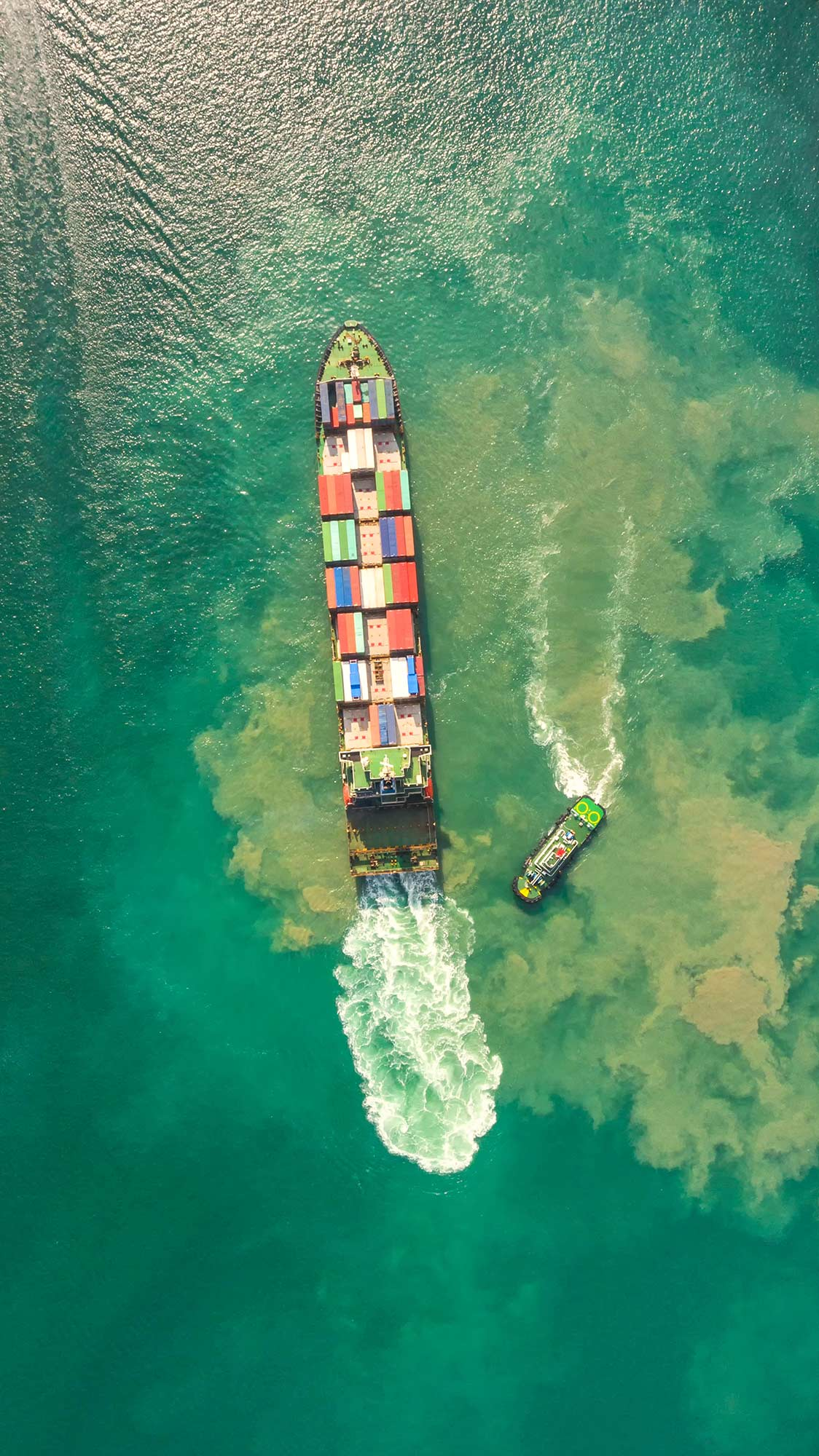 a big ship with containers and a small ship on the green color river